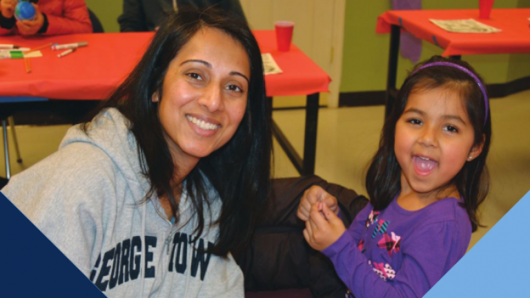 Female student smiling with young little girl during a community service engagement in DC.